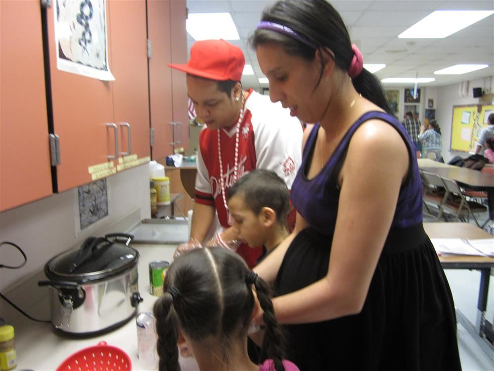 Parents working with their child in ASA to cook a meal