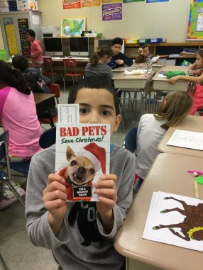 A photo of a 5th grade boy holding a book with his eyes open wide
