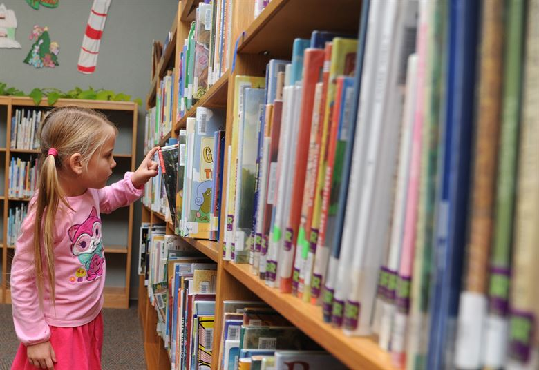 A girl selecting a book from a library shelf